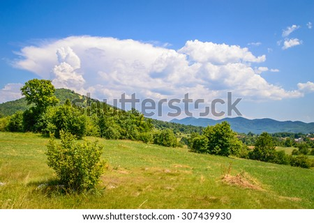Meadow hillside mountain landscape with strong powerful white clouds climbing up from the top of the hill, and mountains in the background. Velebit mountain, Croatia