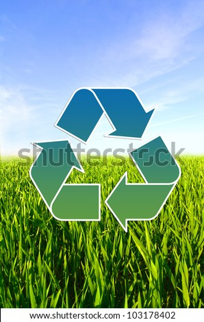 Meadow with green grass and blue sky with clouds and Conceptual recycling sign