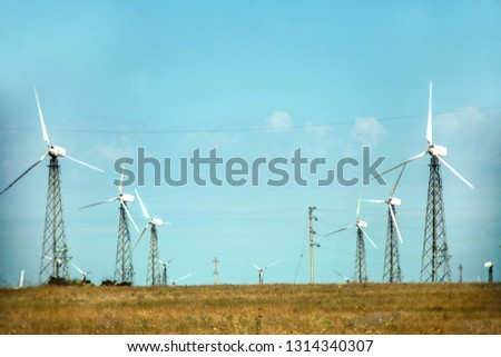 meadow with Wind turbines generating electricity #1314340307