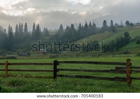 Meadows and village in the mountains in the morning  - Shutterstock ID 705400183