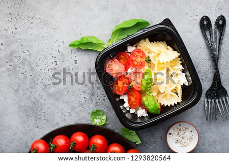 Meal prep. Black lunch boxes. Pasta bows, cherry tomatoes, young cheese, salt, pepper, basil. On a dark background Top view