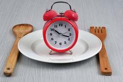 Mealtime concept with an alarm clock in a plate surrounded by wooden cutlery