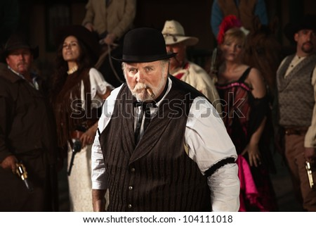 Mean looking man with cigar in old American west costume
