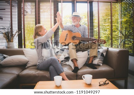Meaningful moments. Lover senior couple sing a song together. Husband playing a guitar and wife is singing. Setup studio shooting.