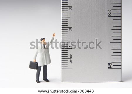 Measure of a man, business figure standing next to a ruler
