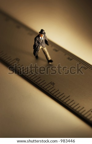 Measure of a man, business figure standing on a ruler