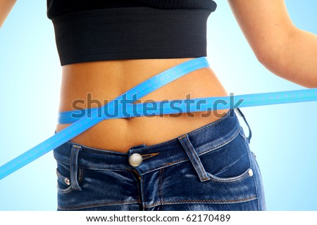 Measure tape around slim beautiful waist. - stock photo