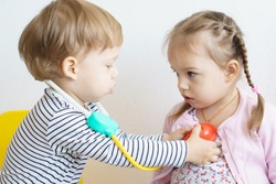 measure the temperature. high temperature, Covid - 19.Two kids play doctor in the nursery.Brother treats his sister, playing dentist, ENT, ophthalmologist Role-playing games check of heartbeat, breath