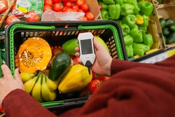 Measurement of nitrate levels in vegetables and fruits. hand holding nitrate tester on a supermarket background. concept of health care and proper nutrition.