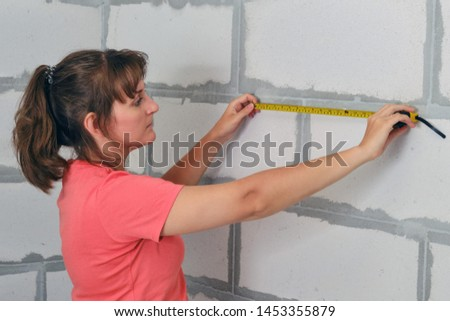 Measurements for the planning of the room and repair of new housing. A woman measures the wall with a ruler close-up. Meter in hand to check the length.