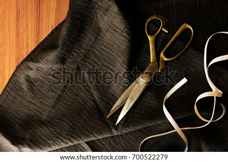 Measuring and cutting textile or fine cloth. Work table of a tailor. Gold scissors, measure tape and black silky fabric. Intentionally shot in retro muted color. #700522279