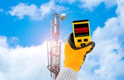 Measuring electromagnetic radiation from a cell tower. The device indicates hazardous radiation with text Danger. Influence of the electromagnetic field on humans concept.