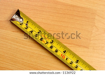 Measuring scale in centimeters and inches over a wooden floor