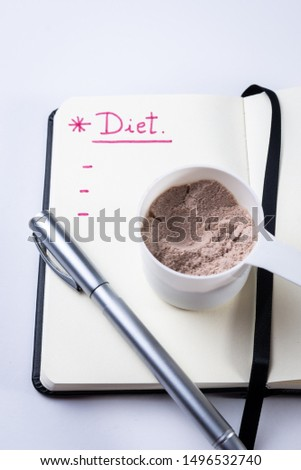 Measuring scoop of whey protein and notebook for diet. Concept of diet, health and exercise