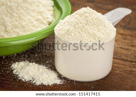 measuring scoop of whey protein powder with a bowl on wooden surface - stock photo