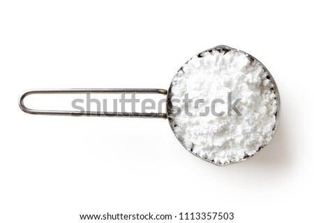 Measuring scoop with powder sugar isolated on white background, top view