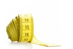 Measuring tape of tailor with indicators in form of centimeters. Yellow rolled measuring tape isolated on white background. Handicraft and tailoring concept. Rolled centimeter ruler of yellow color.