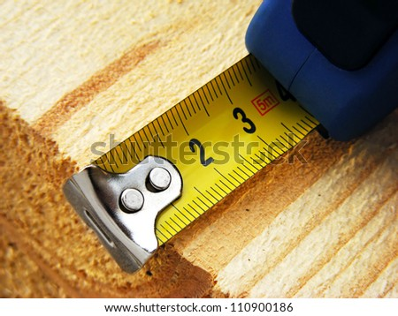 Measuring tape on a wood plank. Build concept.