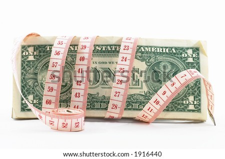 Measuring tape over money, budgeting, measure money, tight budget. Rolled tape on its side.