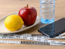 Measuring tape with centimeters and inches, smartphone, pure drinking water, apple and lemon on a brown table. Concept of healthy eating, diet, weight loss and body slim. Front view.