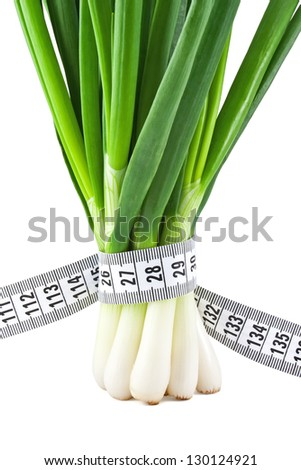 Measuring tape wrapped around a green onions as a symbol of diet
