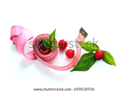 Measuring tape wrapped around a ripe raspberry / Health concept, diet. Fresh with leaves, healthy lifestyle, healthy food  #690658936