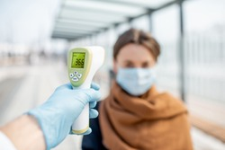 Measuring temperature with infrared thermometer of a young woman in face mask at a checkpoint during an epidemic outdoors. Concept of prevention the spread of the virus