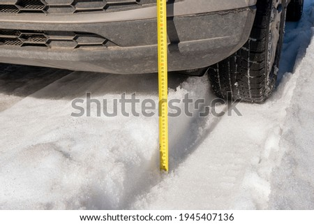 Measuring the vehicle's ground clearance with a ruler. Evaluating the vehicle's off-road capabilities. Winter track. Snow ruts. Sunny day Imagine de stoc ©