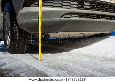 Measuring the vehicle's ground clearance with a ruler. Evaluating the vehicle's off-road capabilities. Winter road Imagine de stoc ©