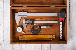 Measuring tools in a wooden case. Accessories for engineers to take measurements. Light background.