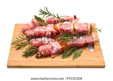 Meat and pepper skewers on a wooden cutting board
