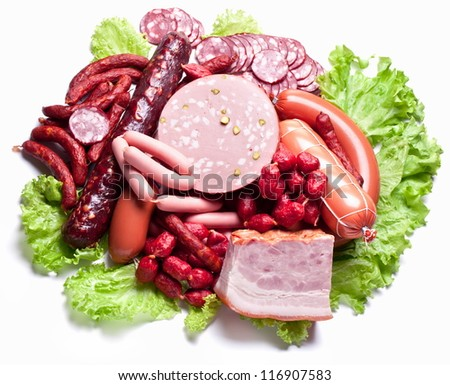 Meat and sausages on lettuce leaves. Isolated on white.
