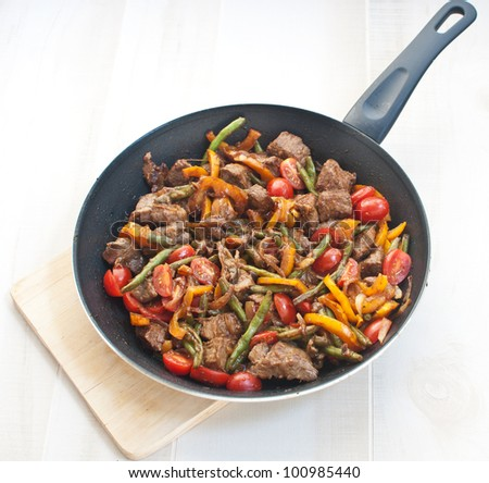 Meat and vegetables in frying pan