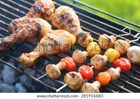 Meat and vegetables on grill. Marinated chicken legs and mushrooms with cherry tomatoes on metal skewers roasted on barbecue grid for summer family dinner