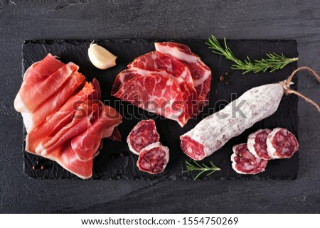 Meat appetizer platter with sausage, and Italian cold cuts. Above view on a slate serving board.