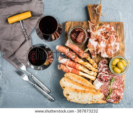 Meat appetizer selection. Prosciutto di Parma, salami, bread sticks, baguette slices, olives, sun-dried tomatoes on rustic wooden board, two glasses of red wine over grey concrete textured backdrop