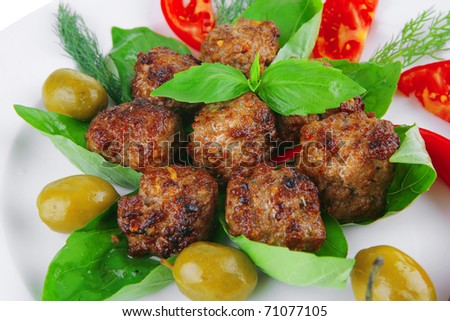 meat balls on basil leaf with olives and tomatoes . shallow dof