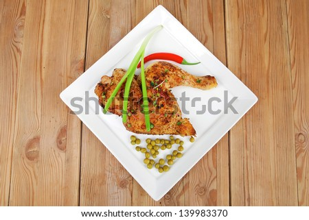 meat : chicken quarters garnished with green sweet peas and red hot pepper on white plate over wooden table