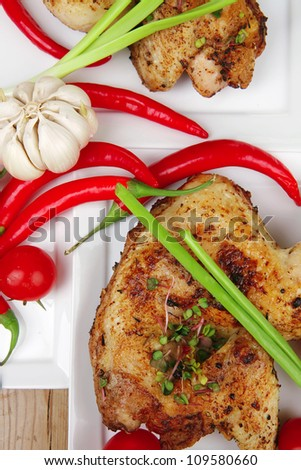 meat : chicken quarters garnished with green sweet peas and red hot peppers on white plates over wooden table