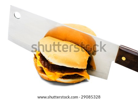 Meat cleaver cutting a burger isolated over white