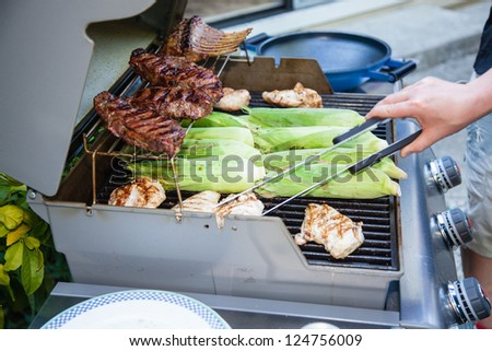 Meat cooking on a charcoal grill in a garden.