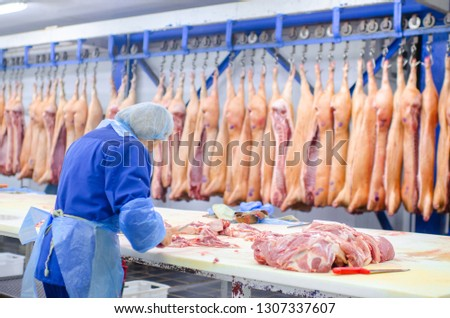 Meat deboning shop. Butcher. Butchers are cutting pork. Line of production of sausage delicacies. Сток-фото ©