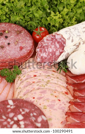 Meat delicatessen plate arranged with cherry tomato and garlic