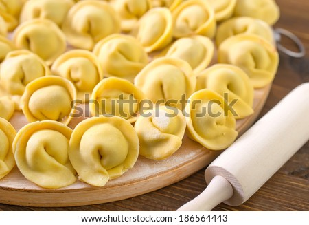 Meat dumplings - russian pelmeni on wooden background - stock photo