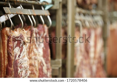 Meat factory. Industrial processing of meat. Slaughterhouse. Cuts of meat hanging on hooks in butchers Сток-фото ©