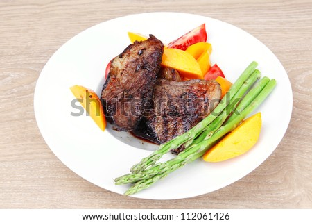meat food : grilled red beef fillet with mango tomatoes and asparagus , served on white dish over wooden table