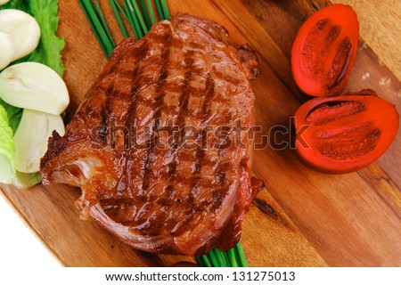 meat food : roast beef garnished with green lettuce and red chili hot pepper on wooden plate isolated over white background