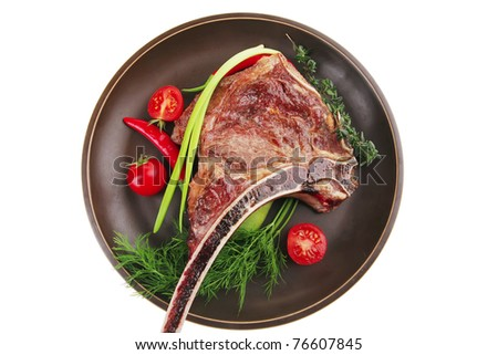 meat food : roast rib on dark dish with thyme pepper and tomato isolated over white background