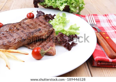 meat food : roast steak boneless with roast onion and red hot peppers, served on green lettuce salad on dish isolated over wooden table #189446528