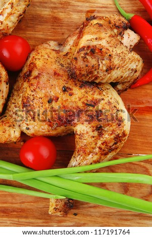 meat food : roasted chicken legs garnished with green sprouts and peppers on wooden plate isolated over white background